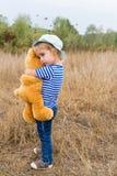 Petite fille mignonne étreignant un grand ours de nounours Photographie stock libre de droits