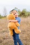 Petite fille mignonne étreignant un grand ours de nounours Photo libre de droits