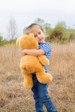 Petite fille mignonne étreignant un grand ours de nounours Images stock