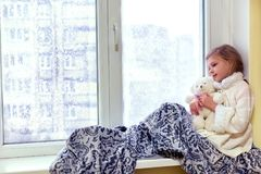 Petite fille mignonne étreignant un ours de nounours Un bébé mignon dans la chambre s'assied à la fenêtre pendant l'hiver Photographie stock