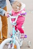 Petite fille mignonne apprenant à monter un vélo photo libre de droits