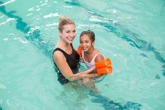 Petite fille mignonne apprenant à nager avec l'entraîneur photographie stock