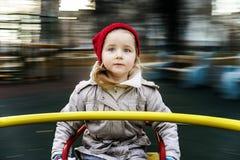 Petite fille mignonne arrondissant sur le manège Photo stock