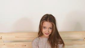 Petite fille mignonne avec de longs cheveux posant dans le studio se reposant sur le banc en bois banque de vidéos