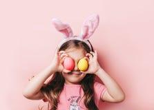 Petite fille mignonne avec des oreilles de lapin sur le fond rose photographie stock