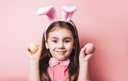 Petite fille mignonne avec des oreilles de lapin sur le fond rose images stock