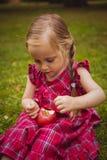 Petite fille mignonne avec des pommes dans une herbe verte Photo stock