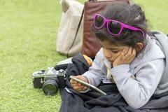 Petite fille mignonne avec des sunglass vérifiant son smartphone photo stock