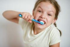 Petite fille mignonne avec des tresses se brossant diligemment les dents photos stock
