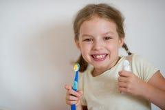 Petite fille mignonne avec des tresses se brossant les dents images libres de droits