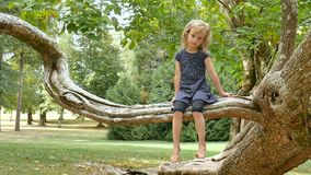Petite fille mignonne avec des yeux bleus et des cheveux blonds se reposant nu-pieds sur la branche d'arbre en parc pendant le jo banque de vidéos