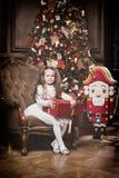 Petite fille mignonne avec le cadeau de Noël près d'un arbre et d'un casse-noix de Noël Photo stock
