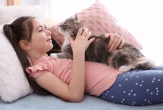 Petite fille mignonne avec le chat se trouvant sur le lit Photo stock