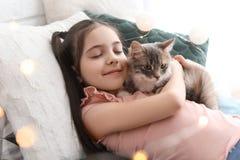 Petite fille mignonne avec le chat se trouvant sur le lit Image stock