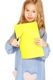 Petite fille mignonne avec les ciseaux et le papier jaune Photographie stock