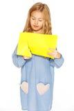 Petite fille mignonne avec les ciseaux et le papier jaune Photos libres de droits