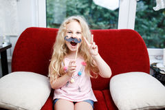 Petite fille mignonne avec les moustaches de papier tout en se reposant sur la chaise rouge à la maison Photo libre de droits