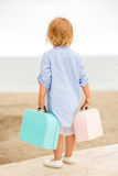Petite fille mignonne avec sa valise à la mer Photo stock