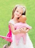 Petite fille mignonne avec son chariot et poupée de jouet photos libres de droits