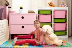 Petite fille mignonne avec un grand ours de nounours se reposant sur le plancher dans Image stock