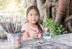 Petite fille mignonne ayant l'amusement à peindre sur la poupée de stuc image libre de droits