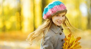 Petite fille mignonne ayant l'amusement le beau jour d'automne Enfant heureux jouant en parc d'automne Enfant recueillant le feui photos libres de droits