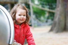 Petite fille mignonne ayant l'amusement sur le terrain de jeu Image stock