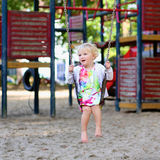 Petite fille mignonne balançant au terrain de jeu Photo stock