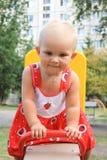 Petite fille mignonne balançant dans la cour de jeu Photographie stock libre de droits