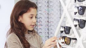 Petite fille mignonne choisissant des lunettes de soleil de l'affichage au centre commercial banque de vidéos
