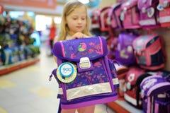 Petite fille mignonne choisissant un cartable avant de commencer des classes Sac à dos adorable d'école d'achats d'élève dans un  photographie stock
