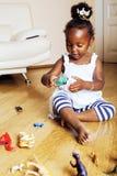 Petite fille mignonne d'afro-américain jouant avec les jouets animaux à ho images stock