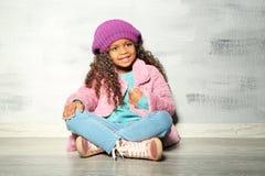Petite fille mignonne d'Afro-américain s'asseyant contre le mur gris Photos libres de droits