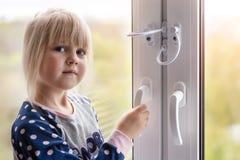 Petite fille mignonne d'enfant en bas âge essayant à la fenêtre ouverte en appartement au bâtiment de haut-tour Serrure de protec photographie stock