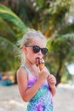 Petite fille mignonne dans des lunettes de soleil avec la crème glacée sur la plage avec des palmiers par la mer Paradis Photo libre de droits