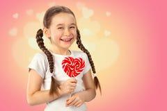 Petite fille mignonne dans l'amour avec le coeur de lucette de sucrerie sur le fond rose Jour du `s de Valentine Photographie stock libre de droits