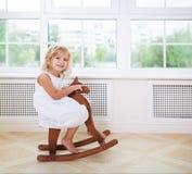 Petite fille mignonne dans la chambre de crèche avec le cheval en bois Photographie stock