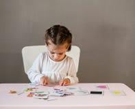 Petite fille mignonne dans la chemise blanche jouant le puzzle photos libres de droits
