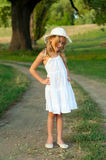 Petite fille mignonne dans la position blanche de robe et de chapeau Images stock