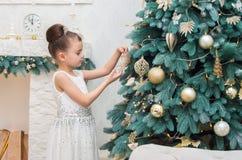 Petite fille mignonne dans une robe blanche décorant un arbre de Noël dessus Images libres de droits
