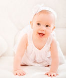 Petite fille mignonne dans une robe blanche et avec le sourire de fleur Image stock