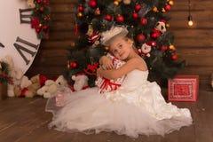 Petite fille mignonne dans une robe intéressante blanche avec un présent image stock