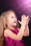 Petite fille mignonne dans une robe rose sur un fond noir Images stock