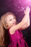 Petite fille mignonne dans une robe rose sur un fond noir Photos stock