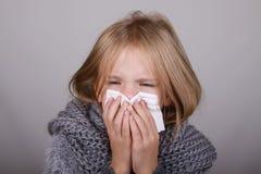 Petite fille mignonne de cheveux blonds soufflant son nez avec le tissu de papier Concept de soins de santé d'allergie de grippe  image stock