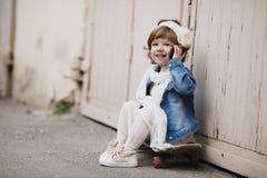 Petite fille mignonne de hippie avec la planche à roulettes photographie stock