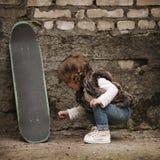 Petite fille mignonne de hippie avec la planche à roulettes Photos libres de droits