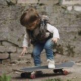 Petite fille mignonne de hippie avec la planche à roulettes Photographie stock libre de droits