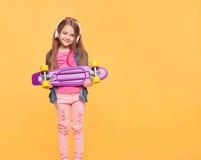 Petite fille mignonne de hippie avec les écouteurs et la planche à roulettes image stock