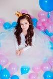 Petite fille mignonne de princesse s'asseyant parmi des ballons dans la chambre au-dessus du fond blanc regarder l'appareil-photo Photos libres de droits